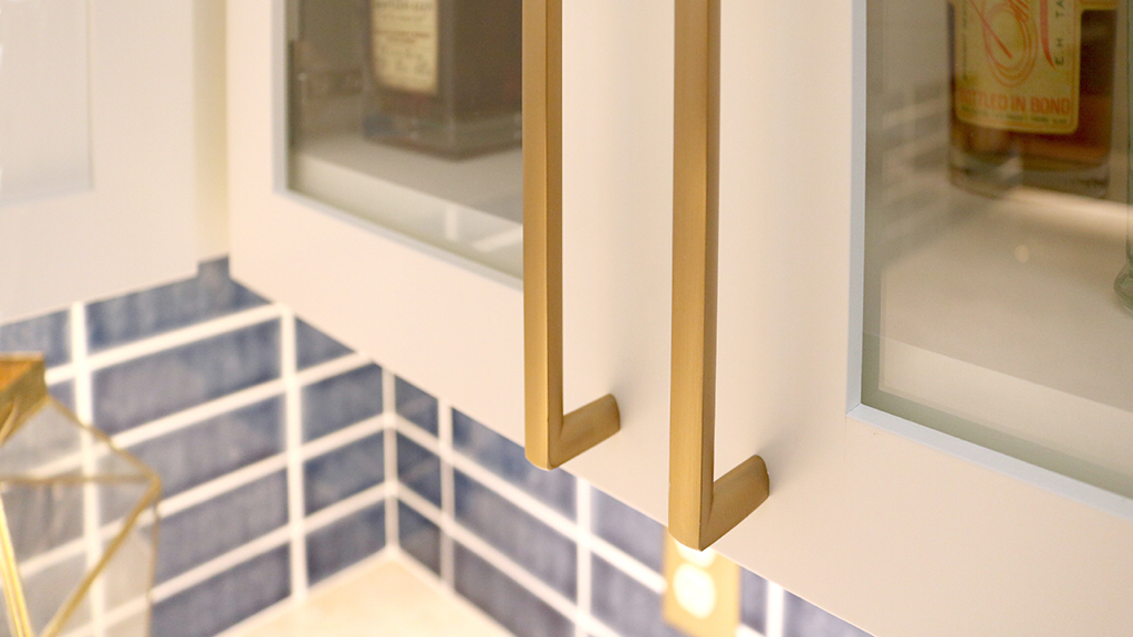 White glass-front upper cabinets with brass hardware